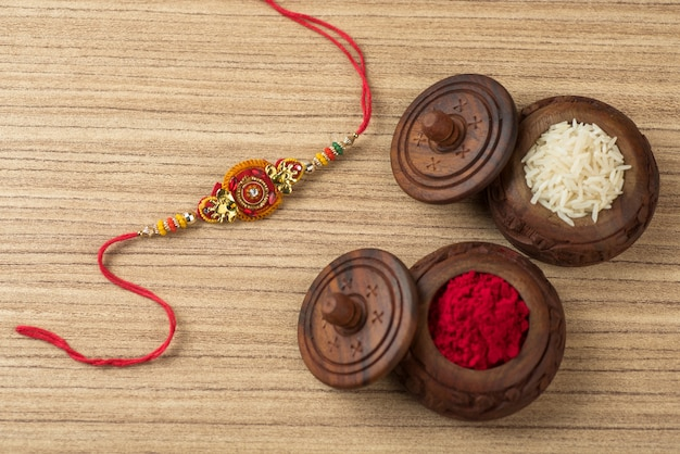 Festival indiano: fundo raksha bandhan com um elegante rakhi, grãos de arroz e kumkum