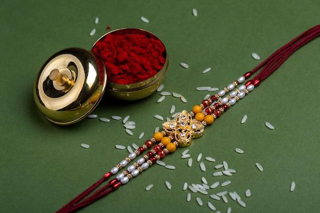 Festival indiano: raksha bandhan com um elegante rakhi, grãos de arroz e kumkum. pulseira tradicional indiana, símbolo de amor entre irmãos e irmãs.