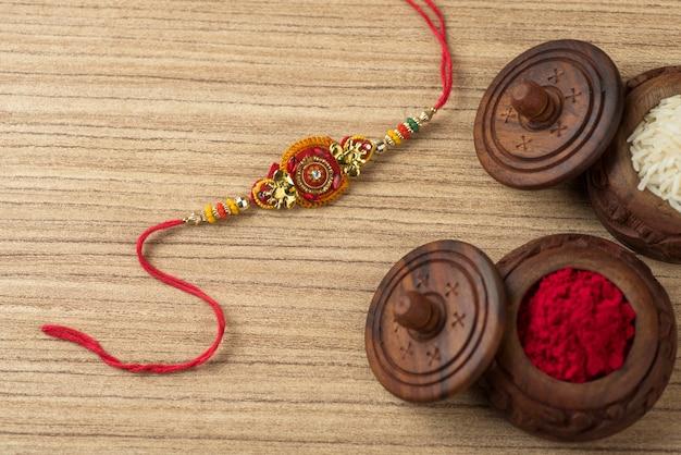 Festival indiano: raksha bandhan com um elegante rakhi, grãos de arroz e kumkum. uma pulseira tradicional indiana que é um símbolo do amor entre irmãos e irmãs.