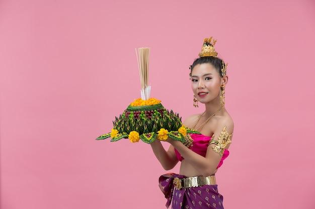 Festival loy krathong; mulher com roupa tradicional tailandesa segurando um flutuador decorado