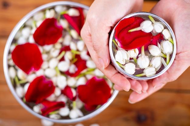 Festival songkran cultura tradicional tailandesa com jasmim e flor rosa para o respeito adulto no ano novo na tailândia.