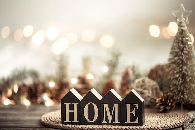Festivo com luzes e a inscrição em casa em uma mesa de madeira. com itens de decoração festiva.