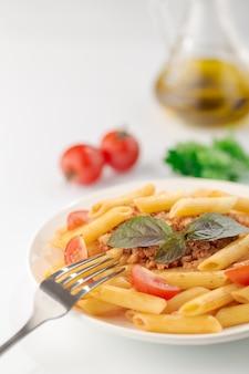 Fettuccine de macarrão à bolonhesa com molho de tomate e manjericão no prato branco sobre branco