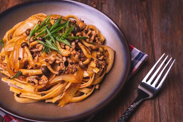 Fettuccine frite com molho de pimenta sichuan chinês com carne de porco, cogumelos e cebola