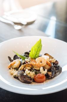Fettuccine preto com camarão, lula e amêijoa. massa de tinta de lulas de frutos do mar.