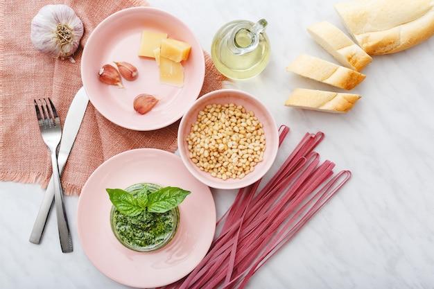 Fettuccine rosa cru e molho pesto com ingredientes em pratos rosa na mesa de mármore branco