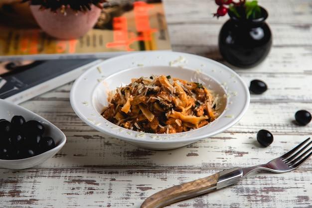 Fettuccini com carne, azeitonas, molho de tomate e queijo ralado