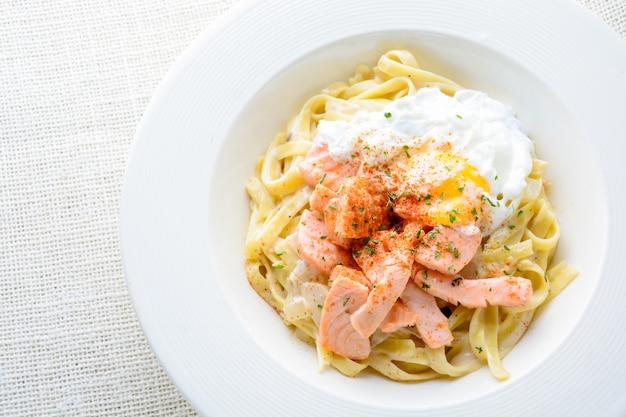 Fettucine com salmão, ovo e queijo parmesão, servido na chapa branca.