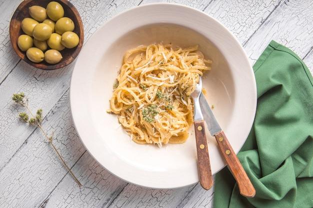 Fettucini alfredo em um prato com azeitonas