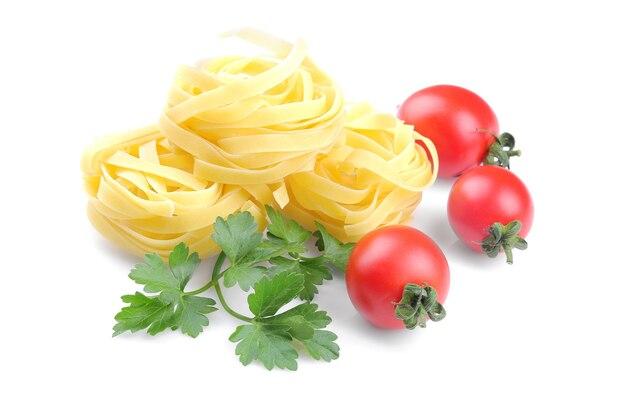 Fetuchini com vários tomates cereja e um ramo de salsa. isolado