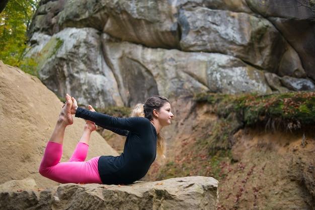Fexible girl está praticando yoga na natureza