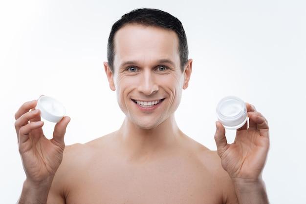 Ficar bonito. retrato de um homem alegre, positivo e sorridente, segurando uma garrafa de creme enquanto usa cosméticos faciais