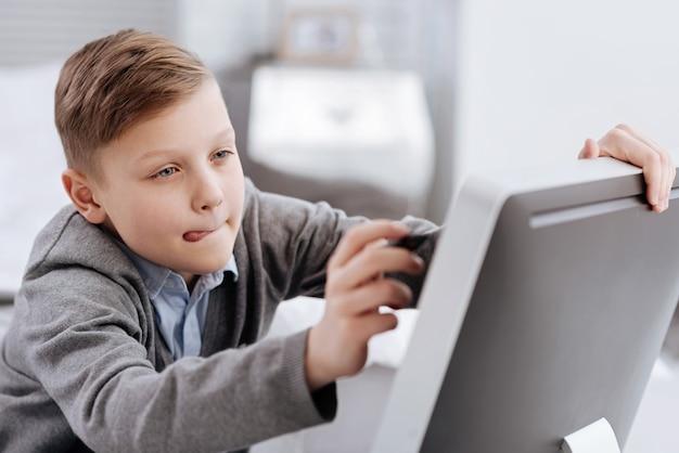 Ficar concentrado. agradável garoto inteligente segurando uma caneta stylus e desenhando na tela digital enquanto se concentra na atividade