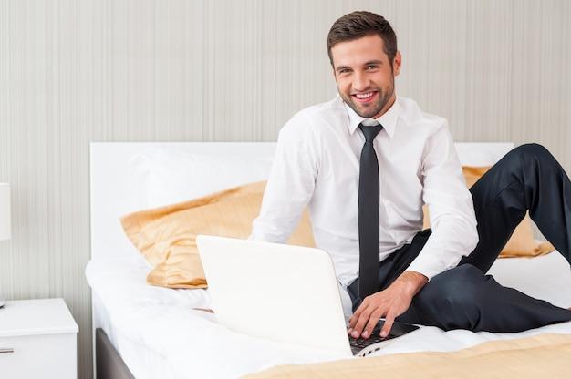 Ficar conectado. jovem bonito de camisa e gravata trabalhando no laptop e sorrindo enquanto está sentado na cama no quarto do hotel