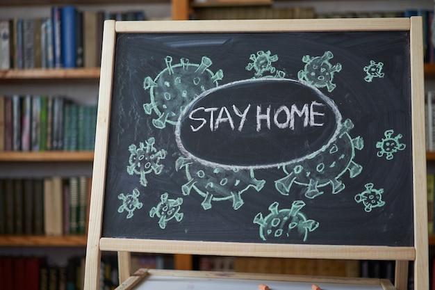 Ficar em casa. aviso de surto. escrito giz branco no quadro-negro em conexão com a epidemia de coronavírus em todo o mundo. texto pandêmico covarde de 19 em fundo preto com espaço livre. bactérias virais desenhadas