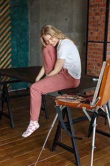 Ficar em casa, conceito de crise criativa: triste artista feminina jovem sentado na mesa
