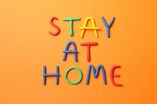 Ficar em casa feito de plasticina na superfície laranja