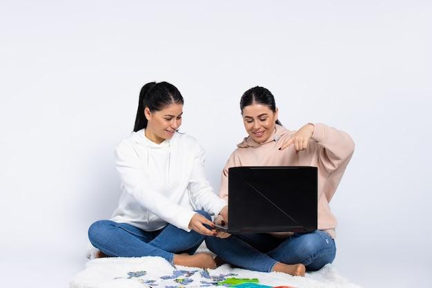 Ficar em casa meninas gêmeas com um laptop e quebra-cabeças sentadas no chão em um branco