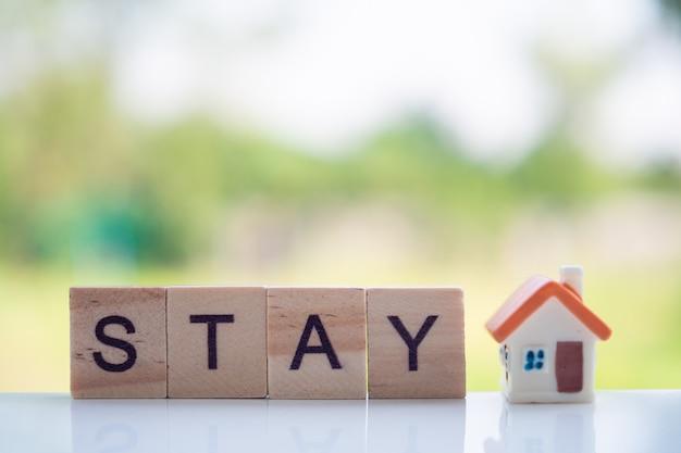 Ficar em casa mensagem feita de letras de madeira e casa em miniatura