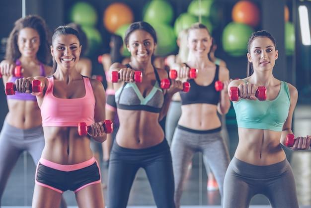 Ficar em forma com um sorriso. jovens mulheres bonitas em roupas esportivas com corpos perfeitos se exercitando com halteres e olhando para a câmera com um sorriso na academia
