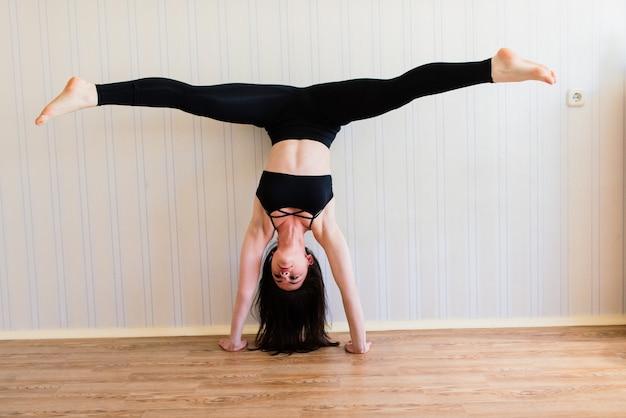 Ficar em forma e saudável. mulher jovem e bonita em roupas esportivas fazendo ioga enquanto relaxa em casa