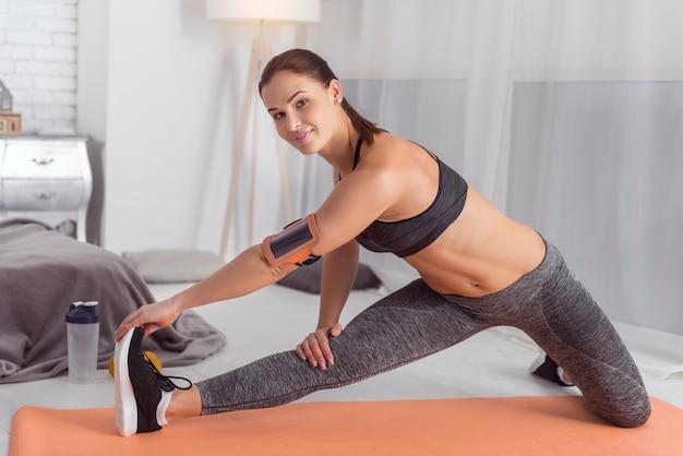 Ficar em forma. linda alerta musculoso jovem de cabelos escuros sorrindo e fazendo exercícios enquanto está sentado no tapete