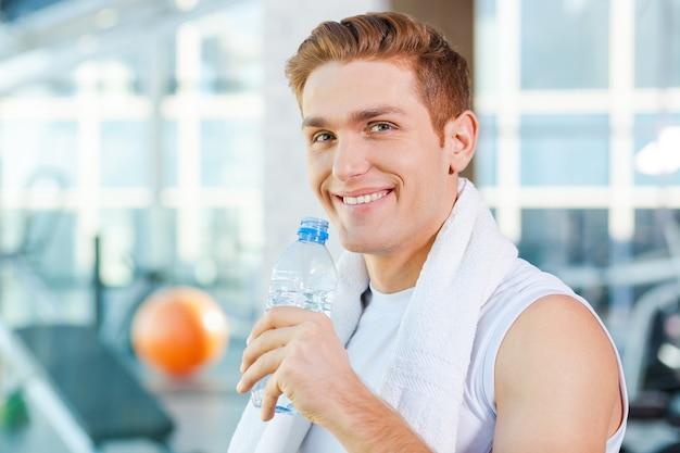 Ficar hidratado. jovem bonito carregando uma toalha nos ombros e bebendo água em pé na academia