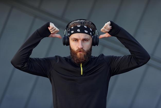 Ficar motivado para um treino intenso ouvindo música com fones de ouvido e luvas para treinar