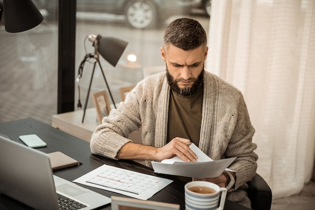 Ficar no gabinete. homem barbudo concentrado preenchendo seu horário de trabalho enquanto carregava um monte de papéis