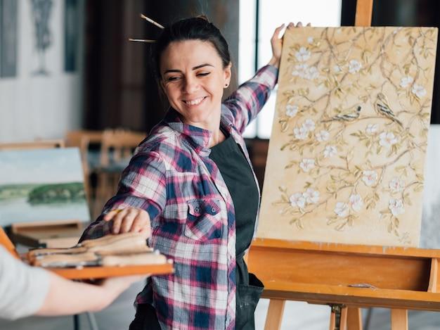 Ficar satisfeito. artista de mulher sorridente com pintura padrão de flores no cavalete. ajuda e assistência do aprendiz.