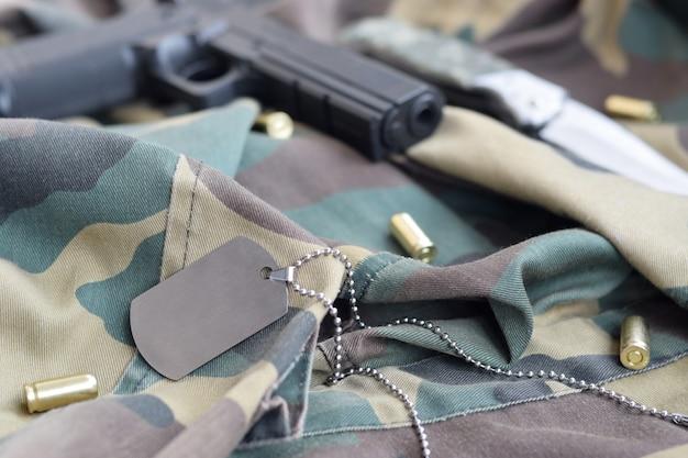 Ficha de identificação dog dog com balas de 9 mm e pistola em tecido dobrado de camuflagem verde