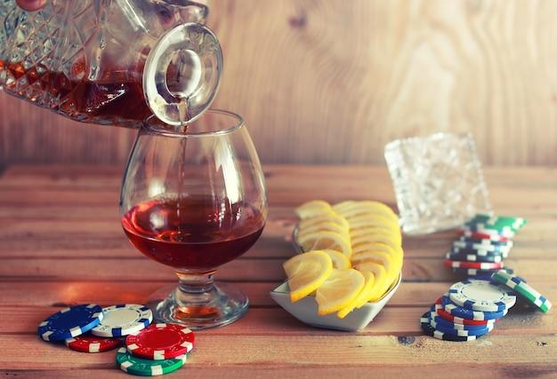 Ficha de pôquer e copo de conhaque