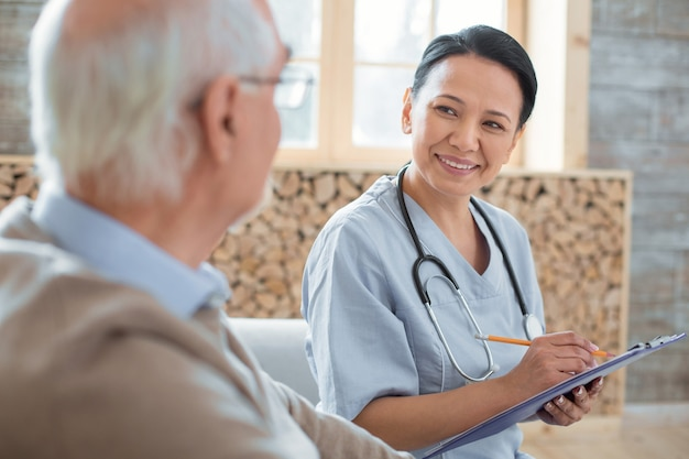 Ficha do paciente. médico alegre e alegre carregando uma prancheta enquanto faz anotações e se comunica com um homem idoso
