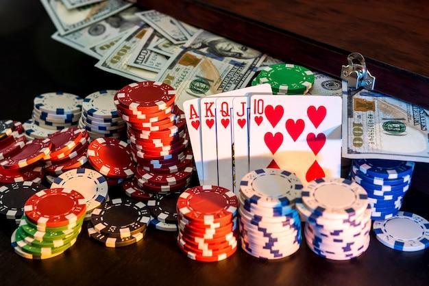 Fichas de cartão de combinação de pôquer e dinheiro na mesa preta.