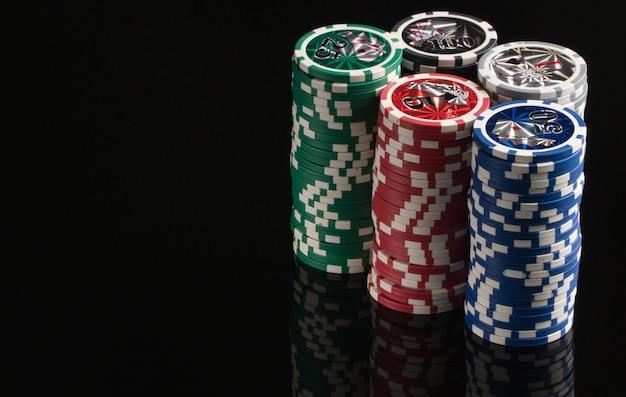 Fichas de cassino em um fundo preto com reflexão. o conceito de jogos de azar e entretenimento. cassino e pôquer