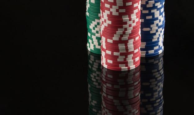 Fichas de cassino em um fundo preto com reflexão o conceito de jogos de azar e entretenimento