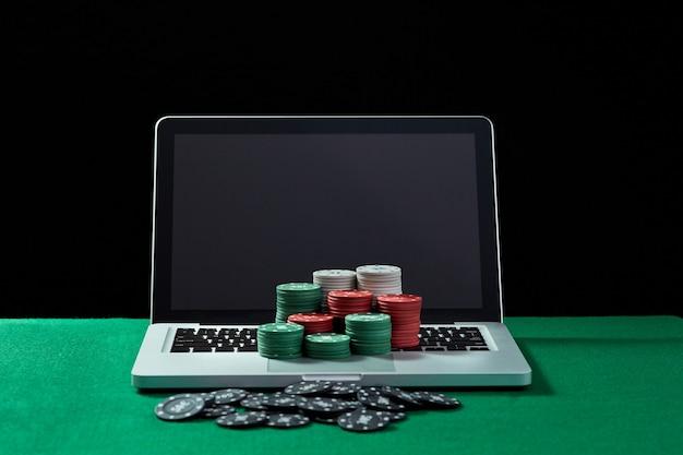 Fichas de cassino no teclado do notebook na mesa verde