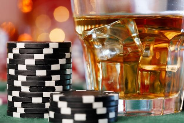 Fichas de jogo ao lado de dados e copo de uísque