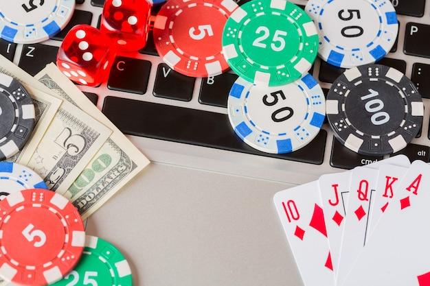 Fichas de jogo com dados, cartas de jogar, dólares americanos no laptop.