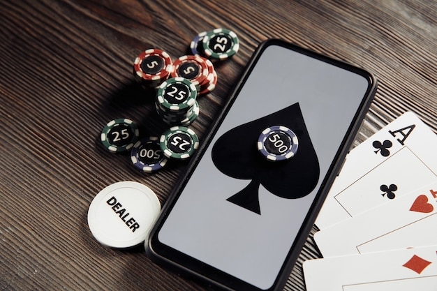 Fichas de jogo, smartphone e cartas de jogar na mesa de madeira.