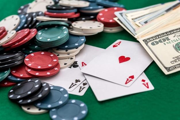 Fichas de pôquer, cartas e dólares em um fundo verde