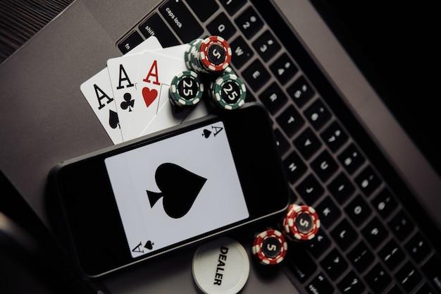 Fichas de pôquer, cartões e smartphone em um teclado cinza. conceito de pôquer online