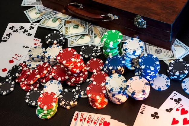 Fichas de pôquer coloridas com cartas de jogar e dólares americanos em fundo escuro.