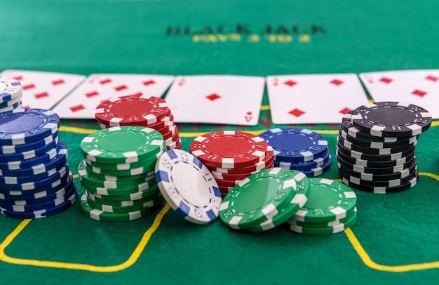Fichas de pôquer com cartas de jogar na mesa para blackjack