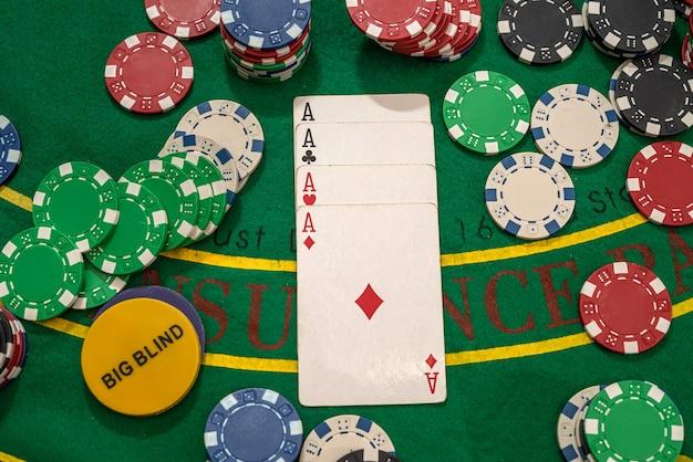 Fichas de pôquer com cartas de jogar na mesa verde do cassino. jogatina