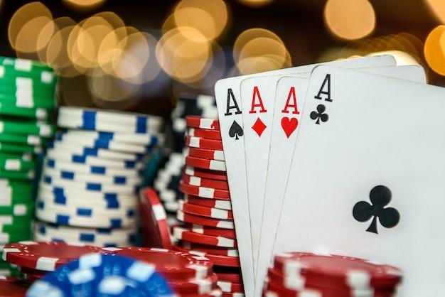 Fichas de pôquer com quatro ases na mesa do cassino