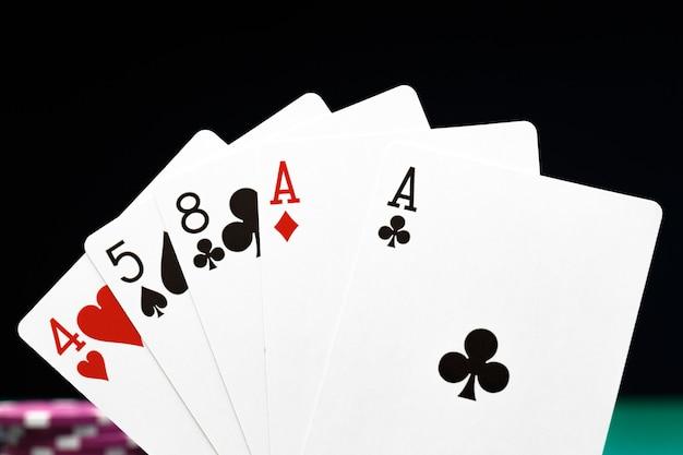 Fichas de pôquer e cartas de jogar no preto