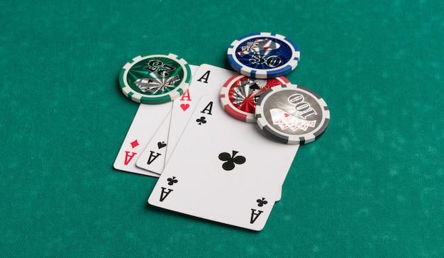 Fichas de pôquer e cartas em um fundo verde o conceito de jogos de azar e entretenimento casino