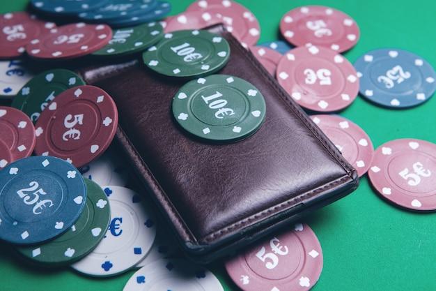 Fichas de pôquer e carteira em uma mesa de jogo em um cassino