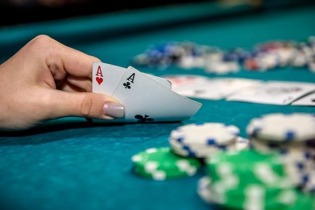 Fichas de pôquer e mãos femininas segurando cartas de jogar